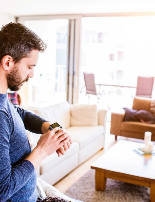 graphicstock-casual-hipster-man-working-from-home-using-smart-watch-standing-in-living-room_rOBqKBSfb